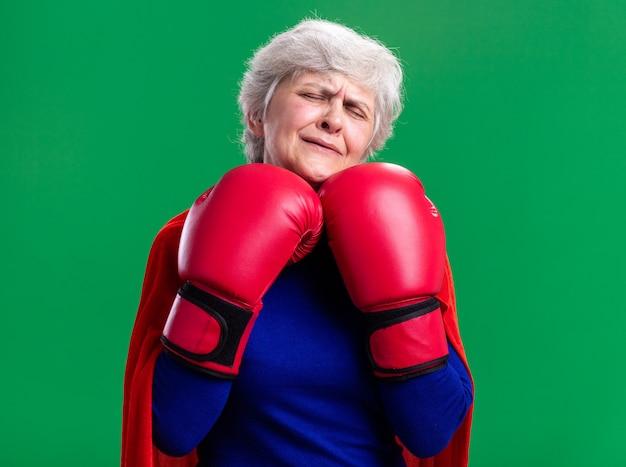 Zdenerwowana starsza kobieta superbohaterka w czerwonej pelerynie z rękawicami bokserskimi płacząca ciężko stojąc nad zielonym tłem