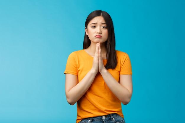 Zdenerwowana urocza, głupia azjatycka dziewczyna modląca się, błagająca o pomoc, dąsająca się, marszcząca brwi, robiąca żałosną minę, trzymająca się za ręce, modląca się o łaskę, przepraszająca uczucia winne smutne, stojące na niebieskim tle