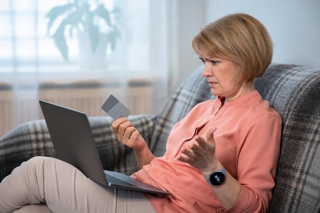 Zdenerwowana zdezorientowana starsza kobieta, zestresowana zmartwiona zdenerwowana pani mająca problem z płaceniem, kupowaniem online, płatnościami kartą bankową zablokowaną kredytem, patrzeniem na ekran, monitor laptopa. oszustwa internetowe