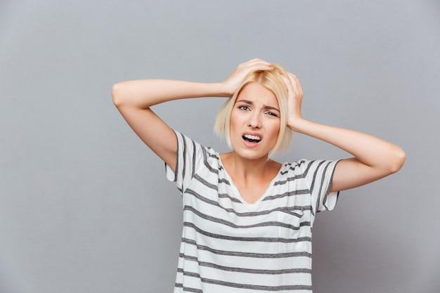Zdenerwowana zestresowana młoda kobieta ma ból głowy nad szarą ścianą