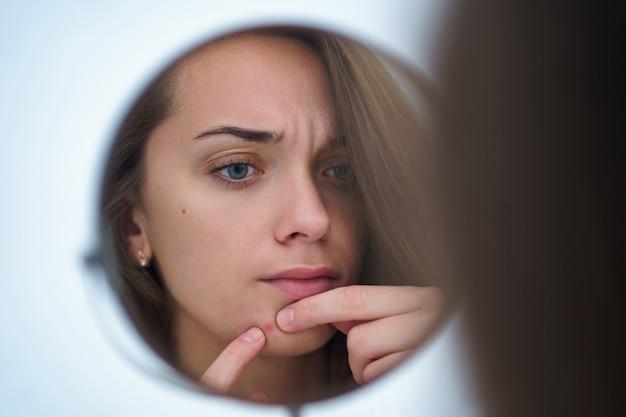Zdenerwowana zestresowana smutna kobieta z trądzikiem i problematyczną skórą ściska krostę w domu za pomocą małego okrągłego lustra