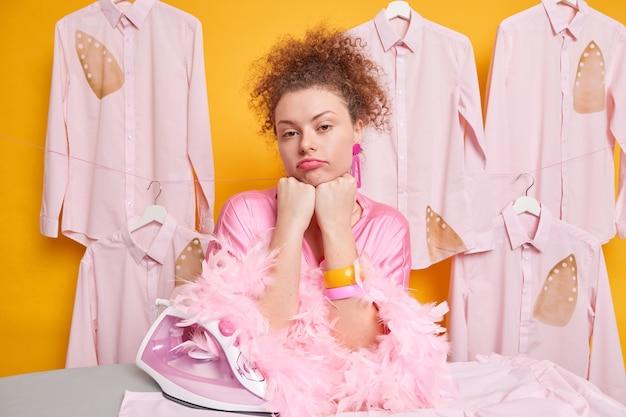 Zdenerwowana zmęczona pokojówka trzyma ręce pod brodą, smutno pochyla się do deski do prasowania, ubrana w domową suknię, nie ma ochoty głaskać ubrań. ludzie prace domowe i obowiązki.
