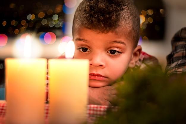 Zdenerwowane dziecko patrząc na świecę. smutny chłopiec obok świec bożonarodzeniowych. uczucie smutku w noc bożego narodzenia. boże narodzenie północy w domu.