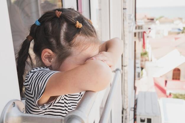 Zdenerwowane dziecko stoi przy otwartym oknie, dziecko zachorowało na wakacjach i jest smutne dziewczyna o azjatyckim wyglądzie...