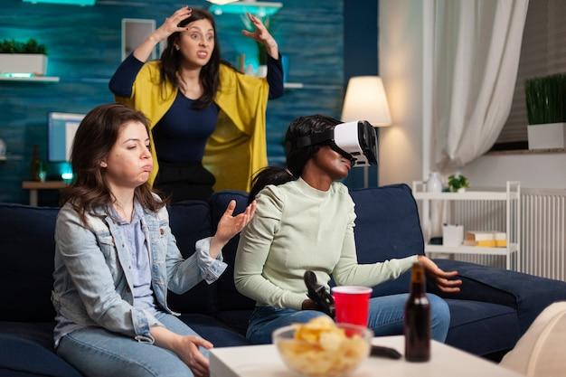 Zdenerwowane wieloetniczne kobiety po przegranej podczas grania w gry wideo w goglach wirtualnej rzeczywistości