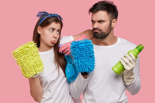 Zdenerwowani europejczycy i mężczyźni marszczą brwi na twarzach, patrząc na siebie, trzymając spray i butelkę detergentu, kolorowe szmaty