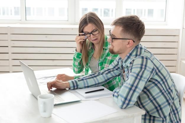 Zdenerwowani mąż i żona biorą pod uwagę całkowite koszty płatności i zakupów dokonanych w ciągu ostatniego miesiąca