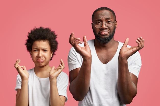 Zdenerwowani ojciec i syn trzymają się za ręce i patrzą z niezadowoleniem, nie mają pieniędzy na zakup, marszczą brwi
