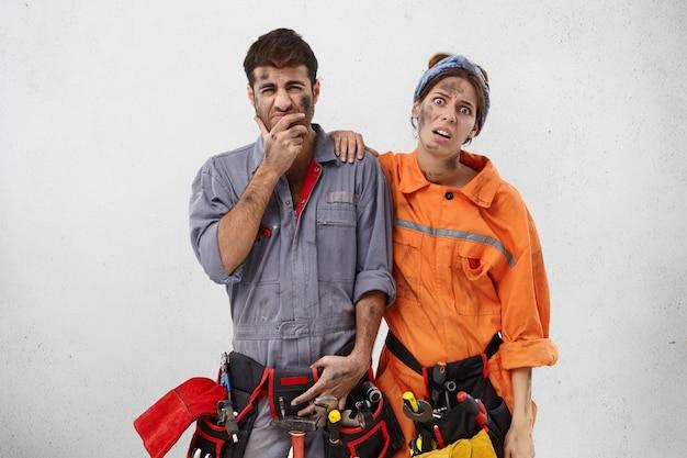 Zdenerwowani pracownicy usług z nieszczęśliwymi minami,