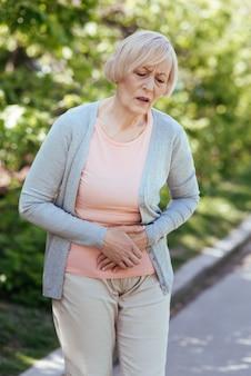 Zdenerwowanie w podeszłym wieku dotyczyło kobiety dotykającej brzucha i wyrażającej negatywne emocje podczas bólu brzucha na świeżym powietrzu