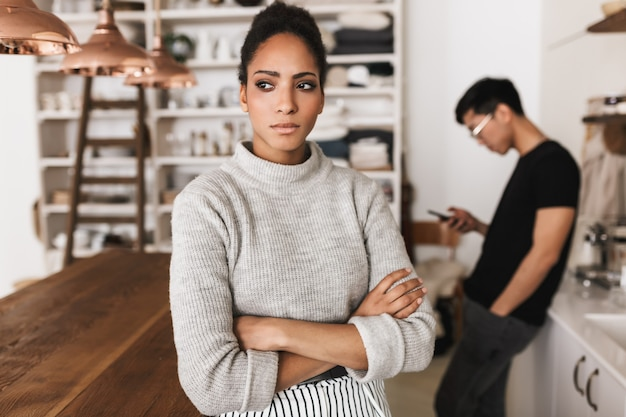 Zdenerwowany african american kobieta trzymając się za ręce razem w zamyśleniu