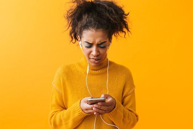 Zdenerwowany afrykańska kobieta ubrana w sweter stojący na białym tle, słuchanie muzyki przez słuchawki, trzymając telefon komórkowy