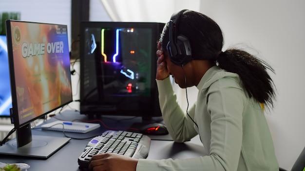 Zdenerwowany afrykański gracz gier wideo przegrywa rywalizację w grach wideo online w profesjonalnym zestawie słuchawkowym