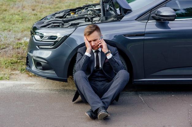 Zdenerwowany biznesmen używać telefonu siedzi na drodze w pobliżu zepsutego samochodu