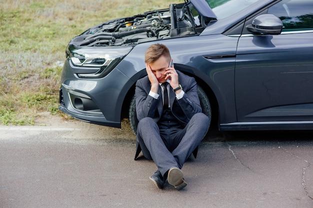 Zdenerwowany biznesmen za pomocą telefonu siedzi na drodze w pobliżu zepsutego samochodu otworzył maskę