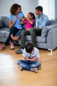Zdenerwowany chłopak siedzi na podłodze z rękami skrzyżowanymi