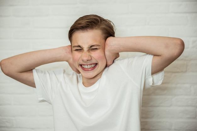 Zdenerwowany Chłopiec Nastolatek Zamykając Uszy I Oczy. Portret Zły Facet Zmęczony Skandalami Lub Plotkami. Koncepcja Negatywnych Emocji Premium Zdjęcia