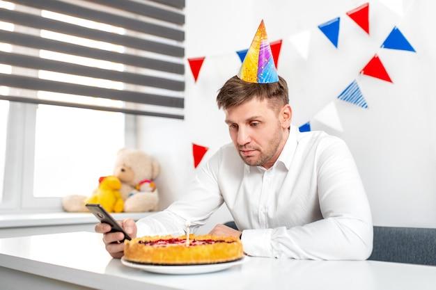 Zdenerwowany czapkę imprezową młody człowiek siedzi na tort urodzinowy i patrzy na niego smutnymi oczami.