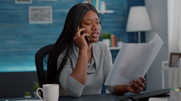 Zdenerwowany czarny student rozmawiający z kolegą przez telefon analizujący papierkową robotę