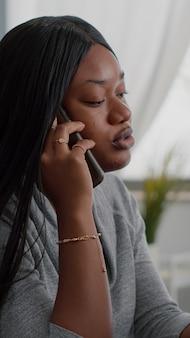 Zdenerwowany czarny student siedzący przy biurku wyjaśniający finansową pracę domową dyskutującą z kolegą
