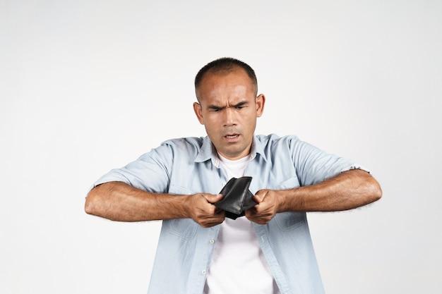 Zdenerwowany dojrzały mężczyzna trzyma do góry nogami i zaglądając do jego pustego portfela na białym tle. kryzys finansowy, bankructwo, brak pieniędzy, zła gospodarka concept.
