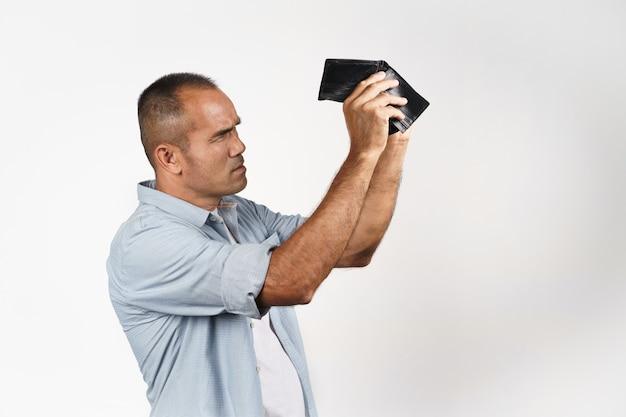 Zdenerwowany dojrzały mężczyzna trzyma i patrząc wewnątrz jego pusty portfel na białym tle. kryzys finansowy, bankructwo, brak pieniędzy, zła gospodarka concept.