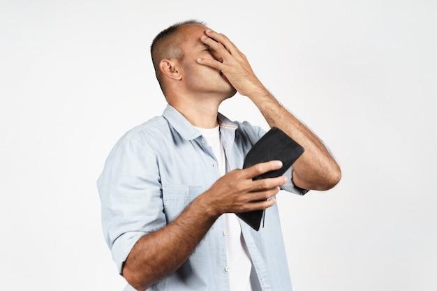 Zdenerwowany dojrzały mężczyzna trzyma jego pusty portfel na białym tle. kryzys finansowy, bankructwo, brak pieniędzy, zła gospodarka concept.