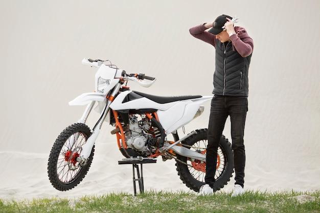 Zdenerwowany dorosły mężczyzna za zepsuty motocykl
