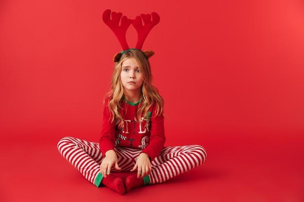 Zdenerwowany dziewczynka ubrana w strój christmas raindeer siedzi na białym tle