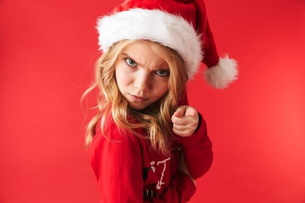 Zdenerwowany dziewczynka ubrana w świąteczny kostium stojący na białym tle, patrząc