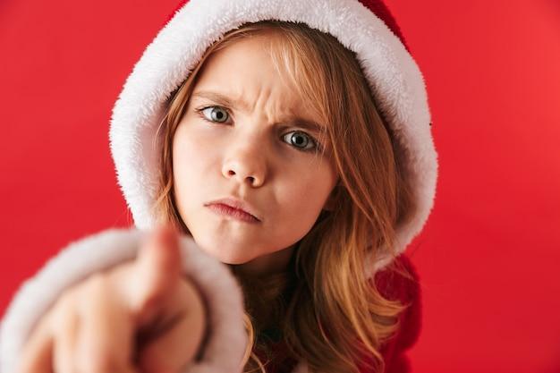 Zdenerwowany dziewczynka ubrana w świąteczny kostium stojący na białym tle, wskazując na przód