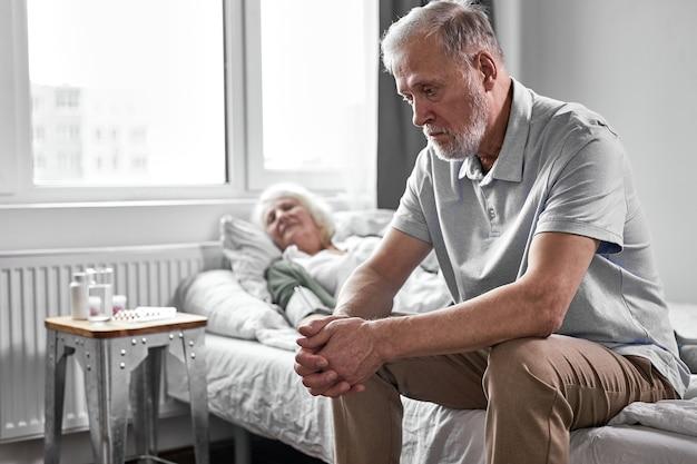 Zdenerwowany emeryt siedzi w depresji, podczas gdy jej chora kobieta cierpi na covid-19, chce, aby żona była zdrowa