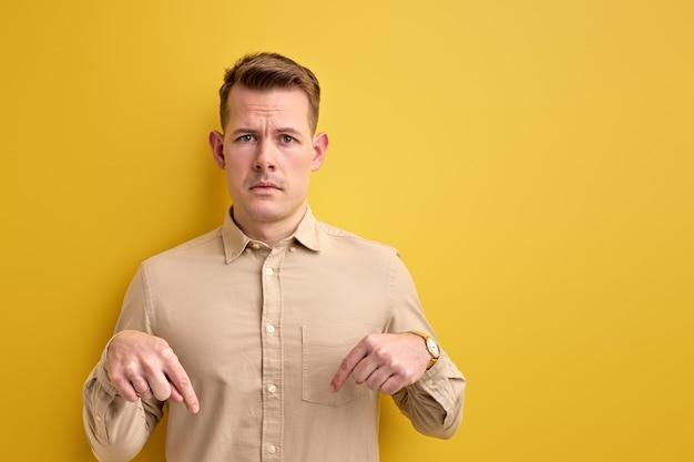 Zdenerwowany facet wskazujący palcem w dół, kopia przestrzeń na białym tle żółta ściana