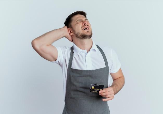 Zdenerwowany fryzjer mężczyzna w fartuchu trzyma kartę kredytową z zamkniętymi oczami stojąc nad białą ścianą