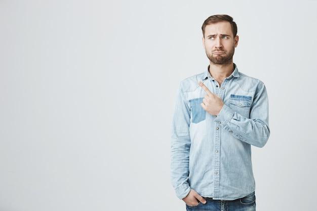 Zdenerwowany i ponury brodaty mężczyzna wskazujący palcem w lewo rozczarowany
