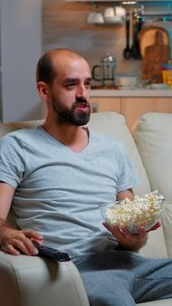 Zdenerwowany kaukaski mężczyzna ogląda samotnie mecz sportowy