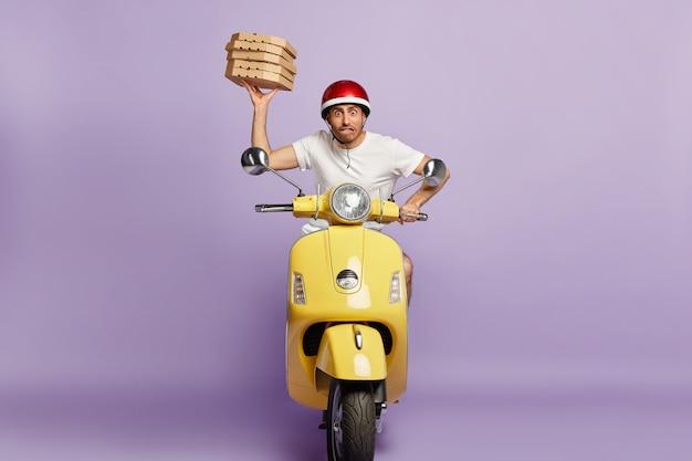 Zdenerwowany kurier prowadzący skuter, trzymając pudełka po pizzy