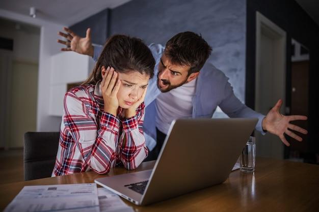 Zdenerwowany mąż krzyczy na smutną żonę, gdy oni płacą rachunki online. w banku nie ma wystarczającej ilości pieniędzy na opłacenie rachunków.