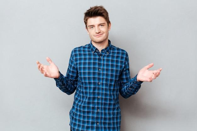 Zdenerwowany mężczyzna nie wie, co robić i gestykuluje rękami