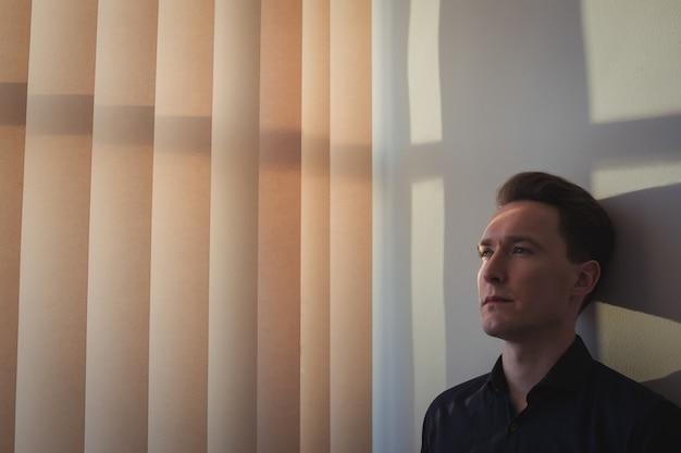 Zdenerwowany mężczyzna oparty na ścianie