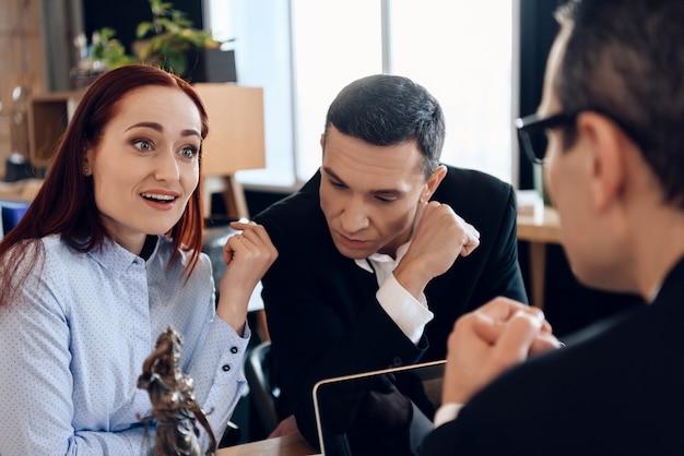 Zdenerwowany mężczyzna siedzi z młodą żoną za adwokatem rozwodowym