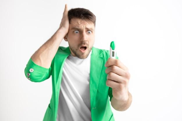 Zdenerwowany mężczyzna szuka testu ciążowego.