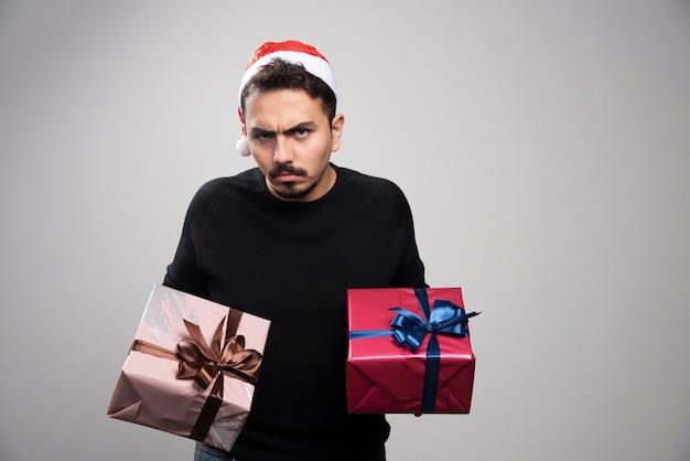 Zdenerwowany mężczyzna w czapce świętego mikołaja trzymający prezenty noworoczne.