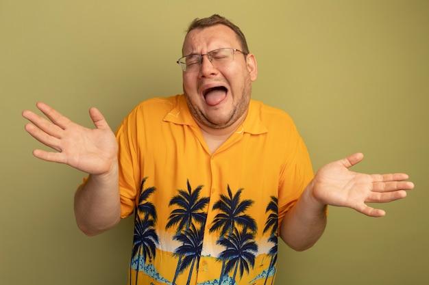 Zdenerwowany mężczyzna w okularach na sobie pomarańczową koszulę krzyczy i wrzeszczy z podniesionymi rękami stojąc nad zieloną ścianą