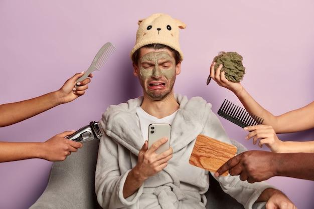 Zdenerwowany mężczyzna z glinkową maską na cerze, niezadowolony z efektu po zabiegach pielęgnacyjnych