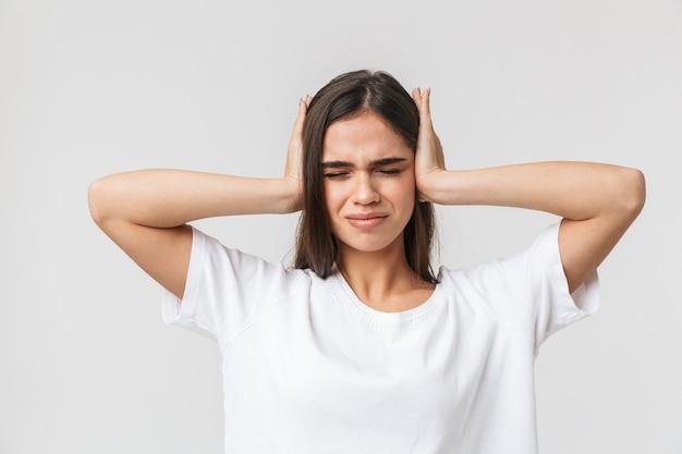 Zdenerwowany młoda kobieta cierpi na ból głowy na białym tle