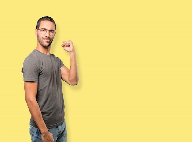 Zdenerwowany młody człowiek robi gest konkurencyjnej