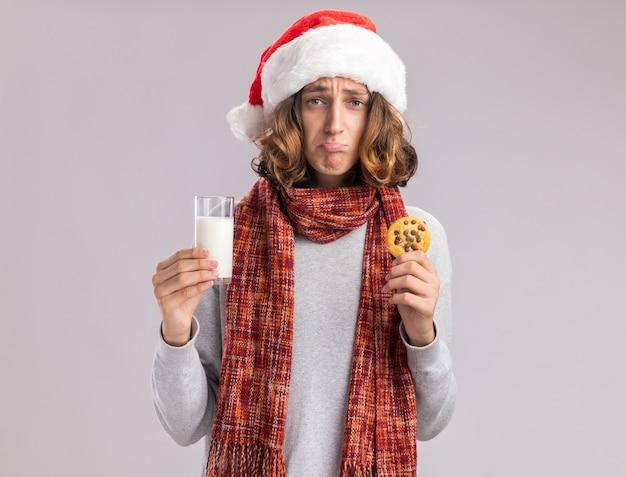 Zdenerwowany młody człowiek ubrany w świąteczną czapkę mikołaja z ciepłym szalikiem na szyi, trzymający szklankę mleka i ciastko ze smutnym wyrazem twarzy ściskający usta stojący nad białą ścianą