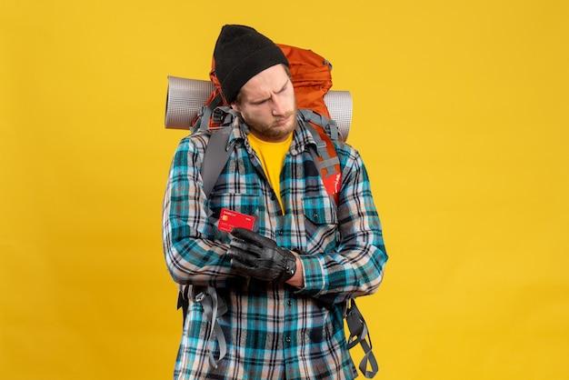 Zdenerwowany młody człowiek z backpackerem posiadającym kartę rabatową