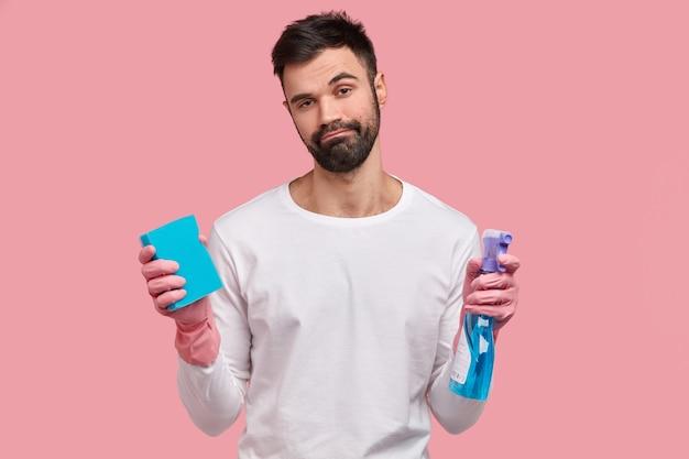 Zdenerwowany młody człowiek z gęstym włosiem, nosi gąbkę i spray, ma senny wyraz twarzy, czuje zmęczenie po wiosennych porządkach w domu w dzień wolny